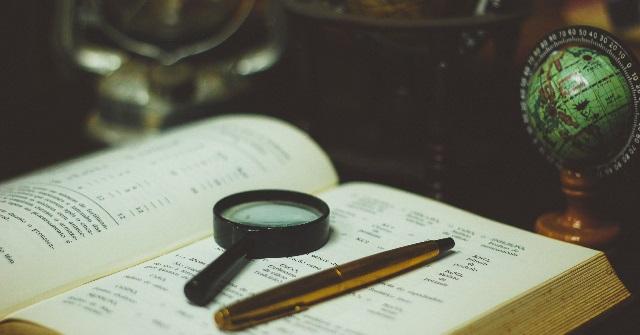 本の上にペンと虫眼鏡