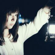 夜にランタンで灯りをともす女性