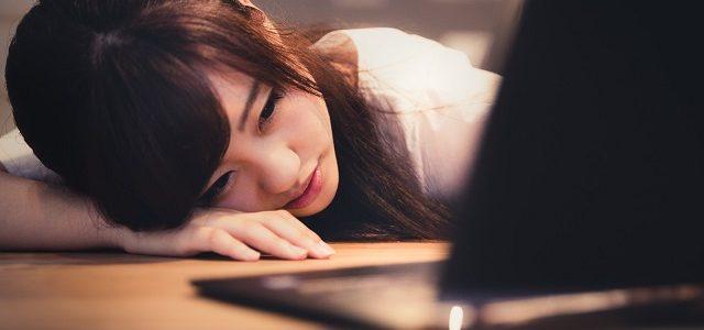 机に倒れ込んで暗い表情でノートPCを見つめる女性