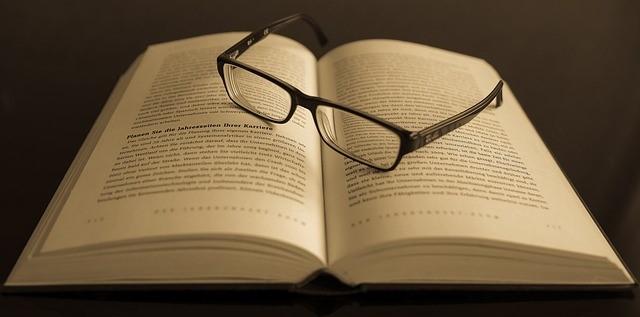 開いた本の上に眼鏡