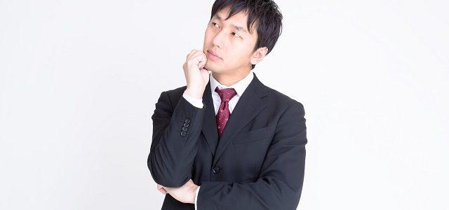 考えるスーツ姿の男性