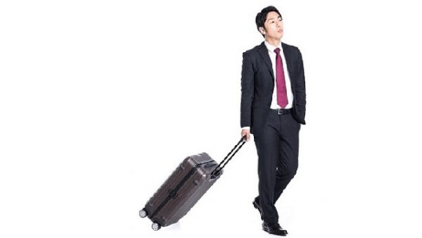 ポケットに手を突っ込みスーツケースを引くスーツ姿の男性