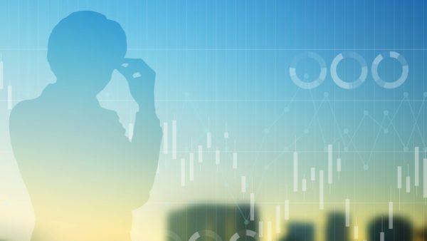 考える人のシルエットと株価