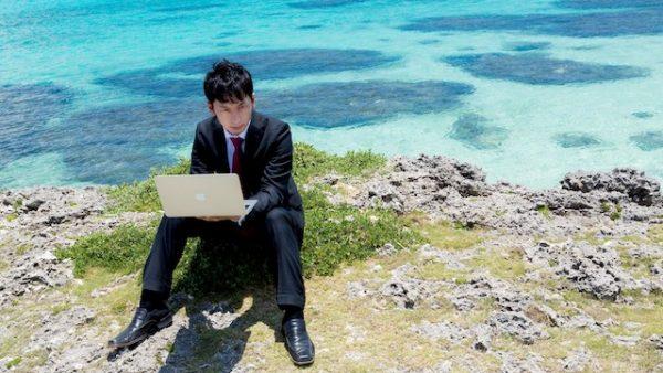 海をバックにノートパソコンを使っているスーツ姿の男性