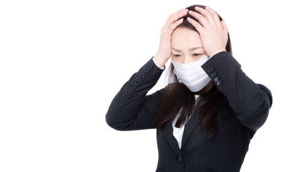 マスクをして頭を抱えるスーツ女性